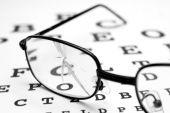 stock photo of snellen chart  - close up of broken glasses and snellen chart - JPG