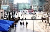 LONDON, UK - MARCH 10, 2014: Canary Wharf square with clocks and office people walking by. Canary Wh