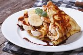 stock photo of crepes  - banana crepes with chocolate on a white plate on the table - JPG