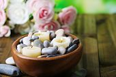 Composition with spa stones, candles  and flowers on  bright background