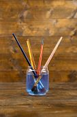 Brushes  in  glass  with water on wooden background