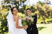 Portrait of a happy newlywed couple with bouquet in the park