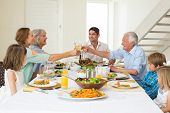 Happy multigeneration family toasting while having meal at dining table