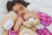 Close-up of a young girl sleeping with stuffed toys in bed at home