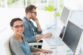 Team of young designers working at desk with woman smiling at camera in creative office