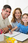 Portrait of happy parents assisting girl in drawing at home