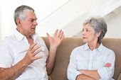 Senior couple sitting on couch having an argument at home in living room