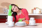 Beautiful young woman wipes clean utensils in kitchen