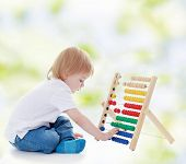 Little boy is counting on the abacus.