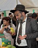 JERUSALEM, ISRAEL - SEPTEMBER 18, 2013: Religious Jew carefully chooses a ritual fruit.