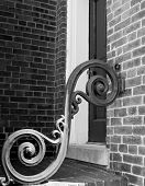 stock photo of scrollwork  - Black & white photo of iron scrollwork on porch stoop in city