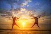 Young couple jumping on the ocean side during amazing sunset. Long-awaited vacation concept.