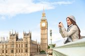 Travel tourist in london sightseeing taking photo pictures near Big Ben. Woman holding smart phone c