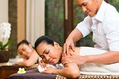 Two Indonesian Asian women in wellness beauty spa having aroma therapy massage with essential oil, l