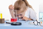 Chemist Looking At The Liquid In Flask