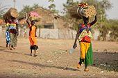 TORIT, SOUTH SUDAN-FEBRUARY 20 2013: Unidentified women carry heavy load on their heads in Torit, So