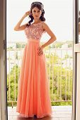 Beautiful Woman With Dark Hair In Coral Dress Posing On Balcony