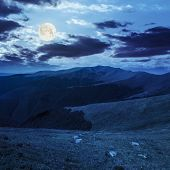 Stones On The Hillside Of Mountain Range In Full Moon Light