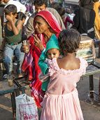 Young Girl Holds Her Baby Sister In The Arm At The Meena Bazaar Market