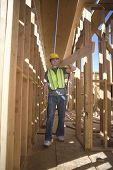 Full length of a male architect carrying wooden beam on shoulder at construction site
