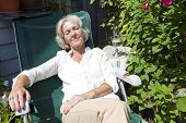 Senior woman relaxing on lounge chair in garden