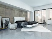 Modern bedroom interior with a double divan bed, paneled wall and large view windows with an urban v