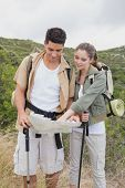 Hiking young couple looking at map on mountain terrain