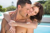 Portrait of a romantic young woman embracing man by swimming pool on a sunny day
