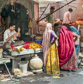 Women Buy Colorful Garlands At The Street Market