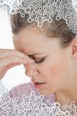 Young woman suffering from headache against snowflakes on silver
