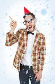 Geeky hipster in party hat pointing against snow falling