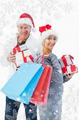 Festive mature couple in winter clothes holding gifts and bags against snowflakes