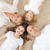 family, children and home concept - smiling family with and two little girls lying in circle on floo