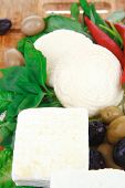 diet food : greek feta white cheese served on wooden plate with basil leaves red hot pepper , black