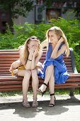 Two beautiful young woman resting on a bench in the park. One cries while the other comforts her.