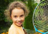 portrait of cute little girl playing tennis in summer