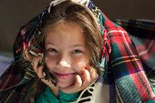 Portrait of cute adorable smiling little girl look out from red plaid