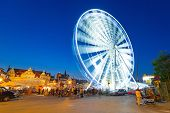 GDANSK, POLAND - 8 AUGUST 2014: Ferris wheel in Gdansk at night with promenade at Motlawa river. Gda