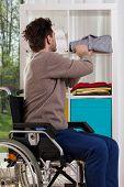 Disabled Man Placing Shirt On Shelf