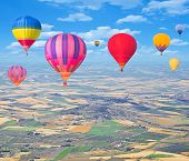Flight of hot air balloons above the countryside.