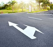 A  traffic arrow signage on an asphalt road indicating a detour left turn.