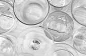High angle shot of assorted glassware forming an abstract pattern. Horizontal format on a white wood