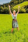 Blonde woman in a dirndl is happy in a green meadow