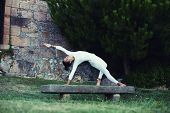 Beautiful girl with slim body practicing yoga sport in the park
