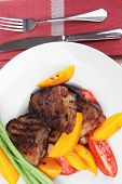 meat food : grilled beef fillet with mango tomatoes and asparagus , served on white dish on red tabl