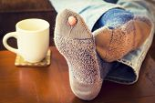stock photo of toe  - Feet propped up on a coffee table  with a pair of worn out socks with a hole and a toe sticking out of them - JPG