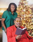 A senior adult man reading scripture in a Christmas-decorated living room.  His wife stands behind looking over his shoulder.