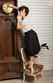 stock photo of pendulum clock  - Beautiful Woman Rewinding A Vintage Clock With Pendulum - JPG