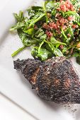 foto of ribeye steak  - Prime ribeye steak served with spinach sauteed in olive oil with garlic and bacon bits - JPG