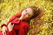Portrait of a cute smiling woman in red coat lying in autumn leaves in park.